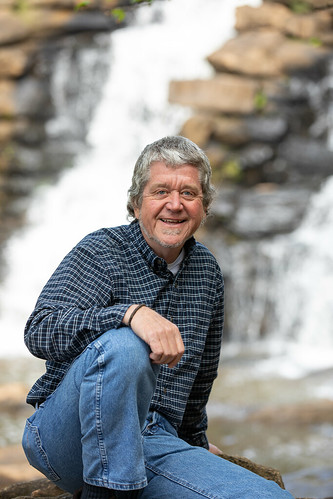 Bill Deutsch sits in front of a waterfall
