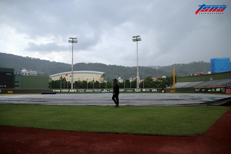 天母棒球場下起驟雨,工作人員已將內野舖上帆布。(林志儒/攝)