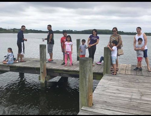 Photo of children and parents fishing from a pier.