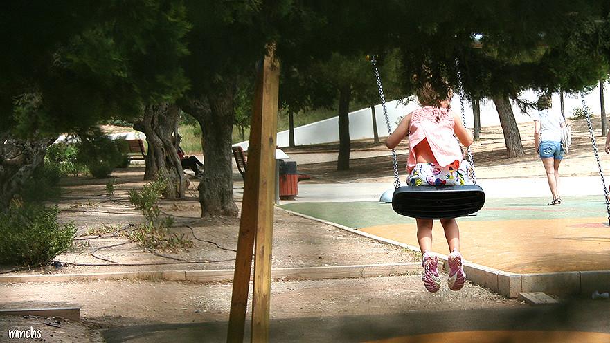 niña columpiándose en el parque central de Paterna