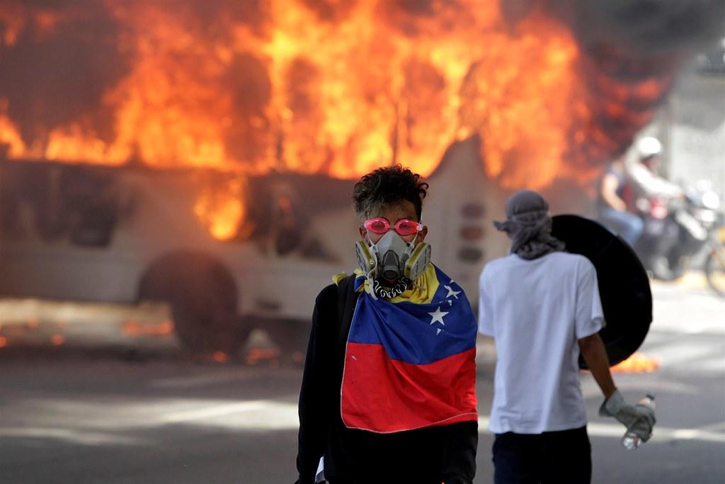 去年5月,一名位于委内瑞拉首都卡拉卡斯的示威者站在燃烧的公车前。(图片来源:REUTERS/Christian Veron)