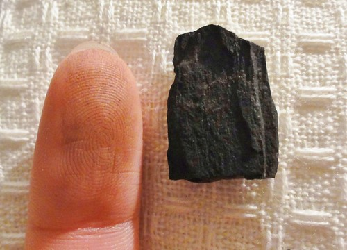 Image shows a fingertip with a faint black smudge; beside it is a fragment of black, rock-hard wood.