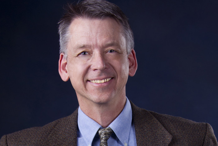 photo of Bruce Carlsten wearing a brown suit jacket and tie with a blue shirt
