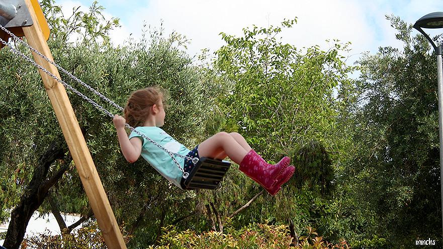 niña jugando en el columpio
