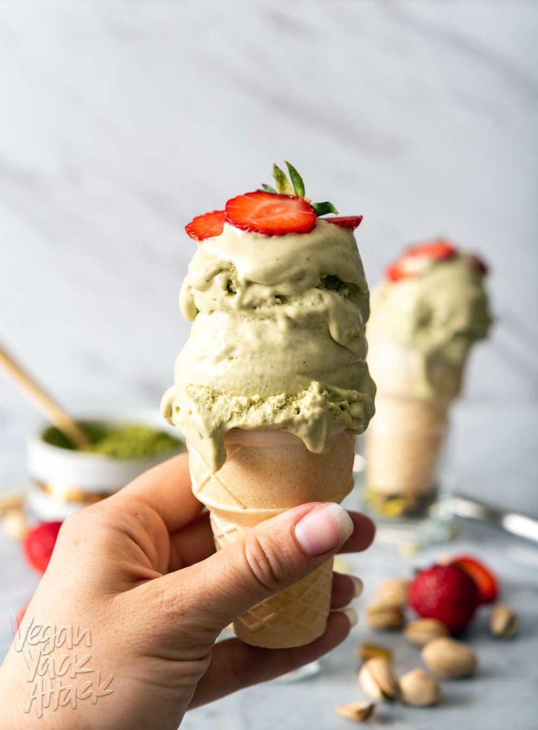 Image of two cones of pistachio matcha ice cream, one being held by a hand, on a marble counter top