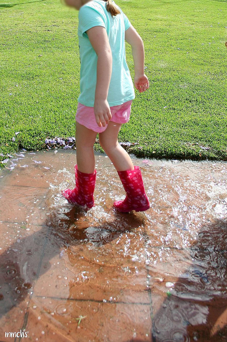 niña jugando en los charcos de agua