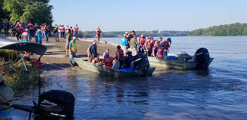 Volunteers load onto boats to head to the banks of the river to clean up trash