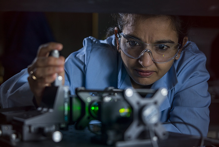 Harshini Mukundan in blue lab coat working with the universal bacterial sensor