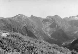 Grassy mountain slope, with guy rope, campsite of John Robert Murrell and Edgar Williams during ascent of Mount Elliot, with view of valley below, and surrounding mountains