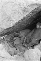 John Robert (Jack) Murrell, standing in an alcove created by large boulders, [bivouac site] Mount Tutoko, Darran Range, Southland Region