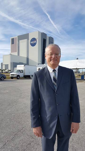 Jim Hansen stands in front of a NASA building.
