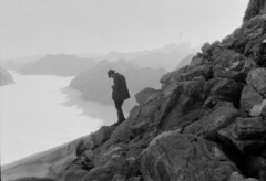 John Robert Murrell, taking a photograph from the summit ridge of Mount Elliot above the Jervois Glacier, showing the north branch of the Clinton River valley filled with fog