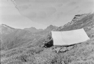 John Robert (Jack) Murrell, sitting outside a tent on a mountain slope, at camp on Mount Elliot, Southland