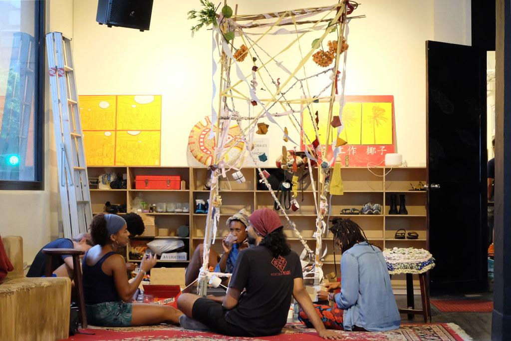藝術家梅塔(Roma Mehta,上右)與康粹蘭(Constance Woods,上左)現場用廢棄物進行藝術創作,用無法跨越的門反思廢棄物氾濫的現況。攝影:陳文姿