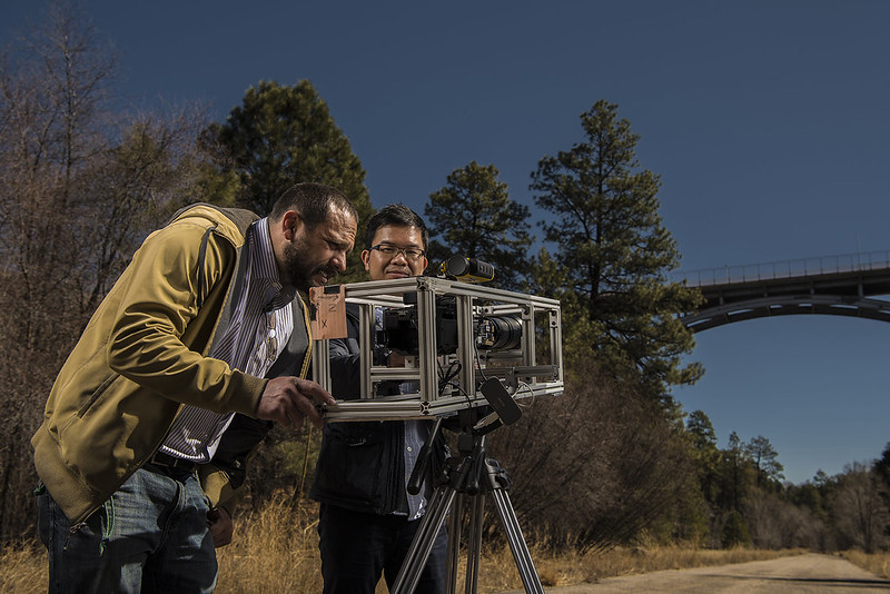 Yongchao Yang, left, and David Mascareñas make adjustments to the video camera used in their video-based technology to measure and assess the response of structures to dynamic loads.