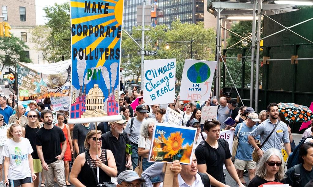 """今年气候行动峰会前夕,示威者高举""""企业污染者付出代价""""标语于纽约游行。(图片来源:Michael Brochstein/SOPA Images)"""