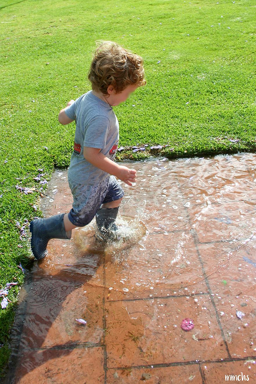 niño saltando en los charcos de agua