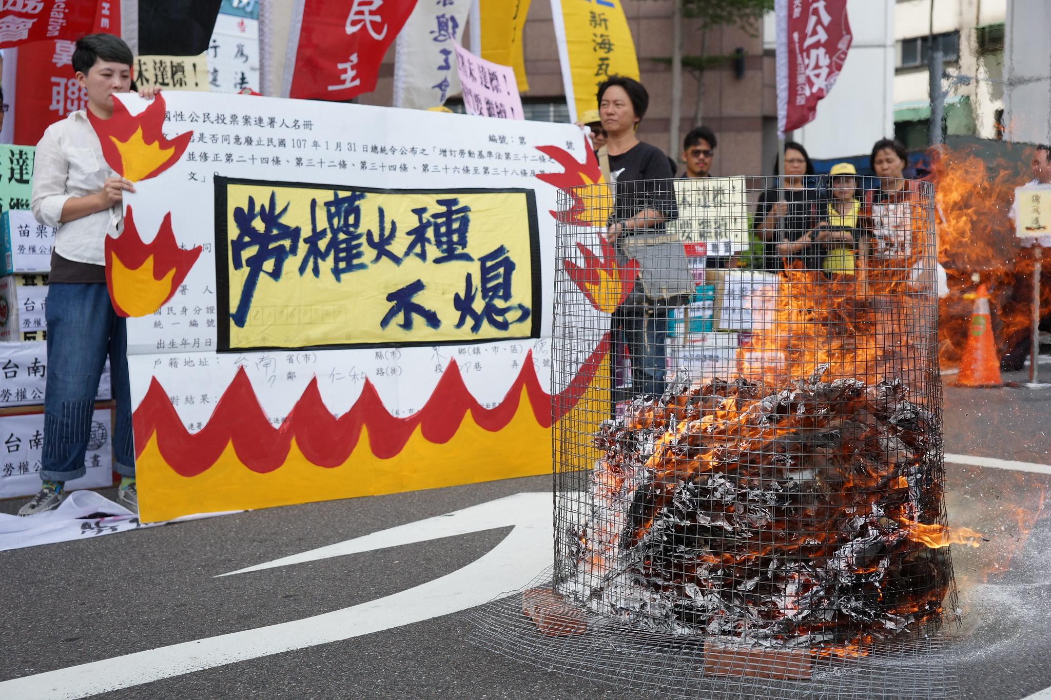 劳公盟在现场焚烧部分公投连署书,并表示后续也会废弃全数连署书,保护连署人个资。(摄影:王颢中)