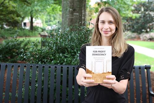 Loka Ashwood sits outside and holds her book