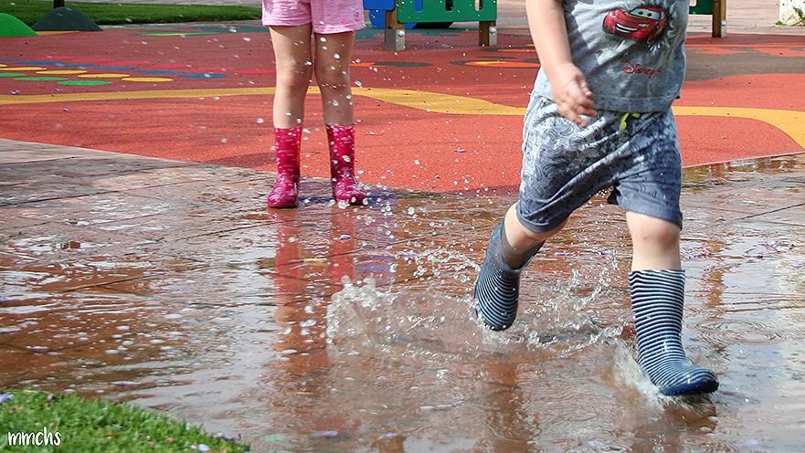 Niños jugando y saltando en los charcos de agua