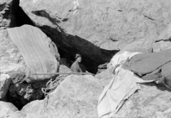 John Robert (Jack) Murrell, standing in a chasm between large boulders [bivouac site], with tent spread out on rocks above, Mount Tutoko, Darran Range, Southland Region