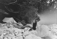 John Robert (Jack) Murrell, standing among boulders near a campsite, Tutoko Valley, Southland Region