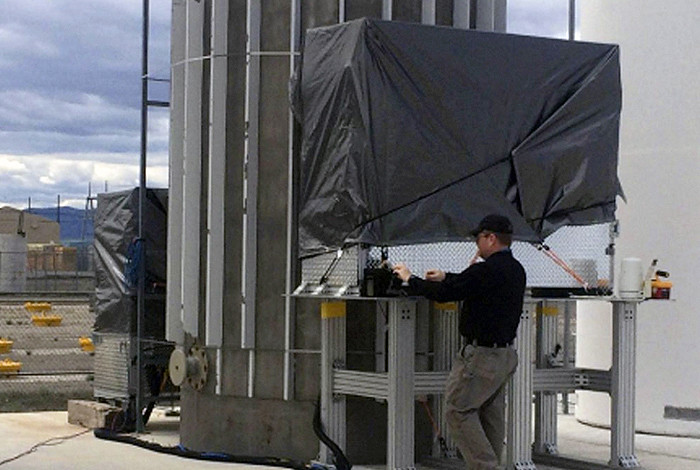 A person in with a black shirt and hat standing next to the muon tracker