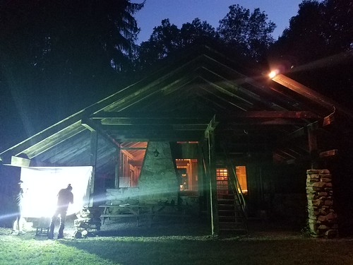 students outside a wooden dorm or lodge, collecting insects at a sheet that hangs from rope. it is night time