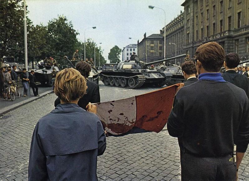 Manifestantes con una bandera checoslovaca llena  de sangre, ante los tanques y blindados que intentaban alcanzar la sede  de Radio Praga.