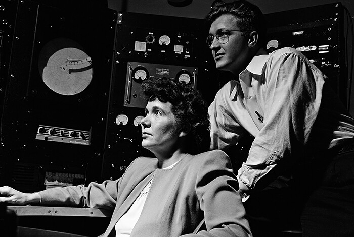 A black and white photo of a man and woman in a control room looking at something out of the frame.