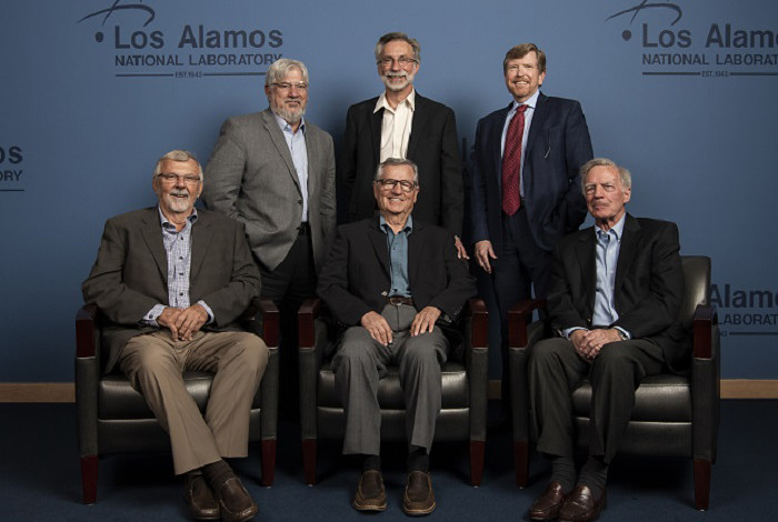 A group of six men pose for a photo in front of a blue wall embossed with the LANL logo.