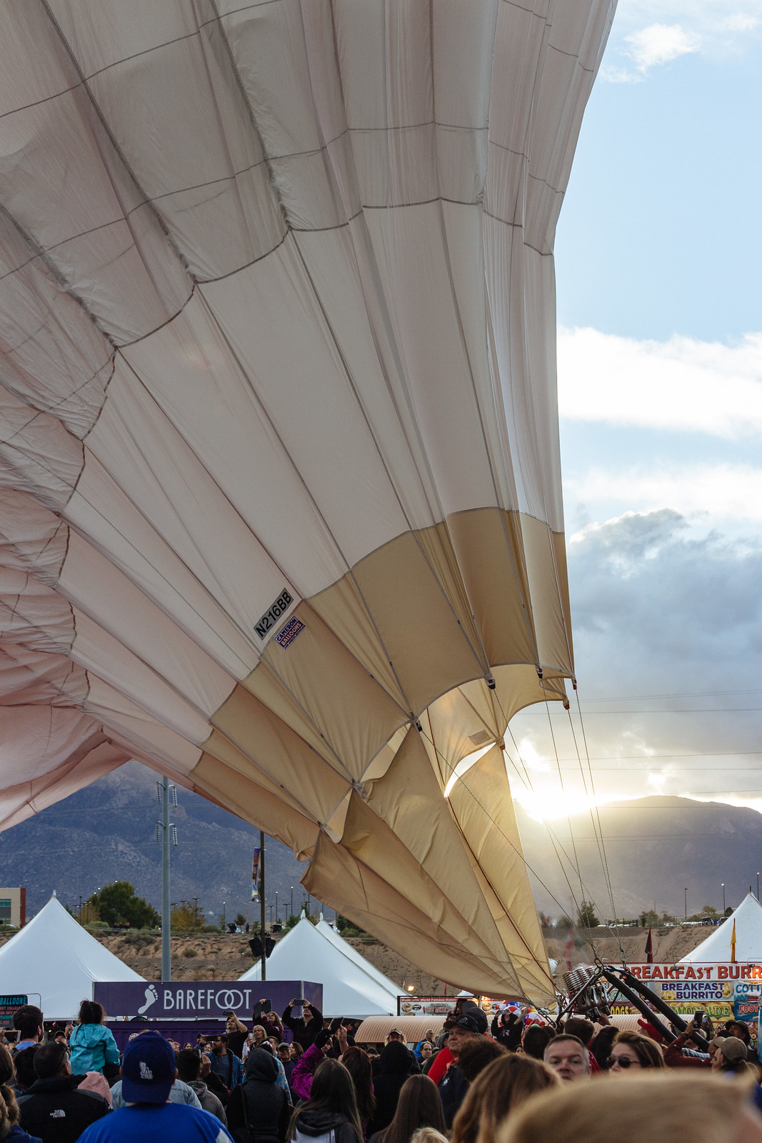 The sun shining over the mountains and on a white half-inflated balloon at the Albuquerque International Balloon Fiesta