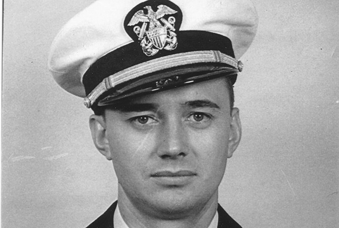 Black and white photo of a man's shoulders and head; he is in a Navy uniform.