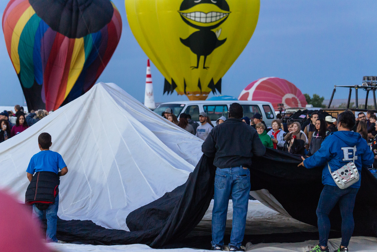 A family helps unroll the fabric of a balloon envelope at the Albuquerque International Balloon Fiesta