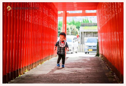 神社の赤い鳥居の中を走る2歳の男の子