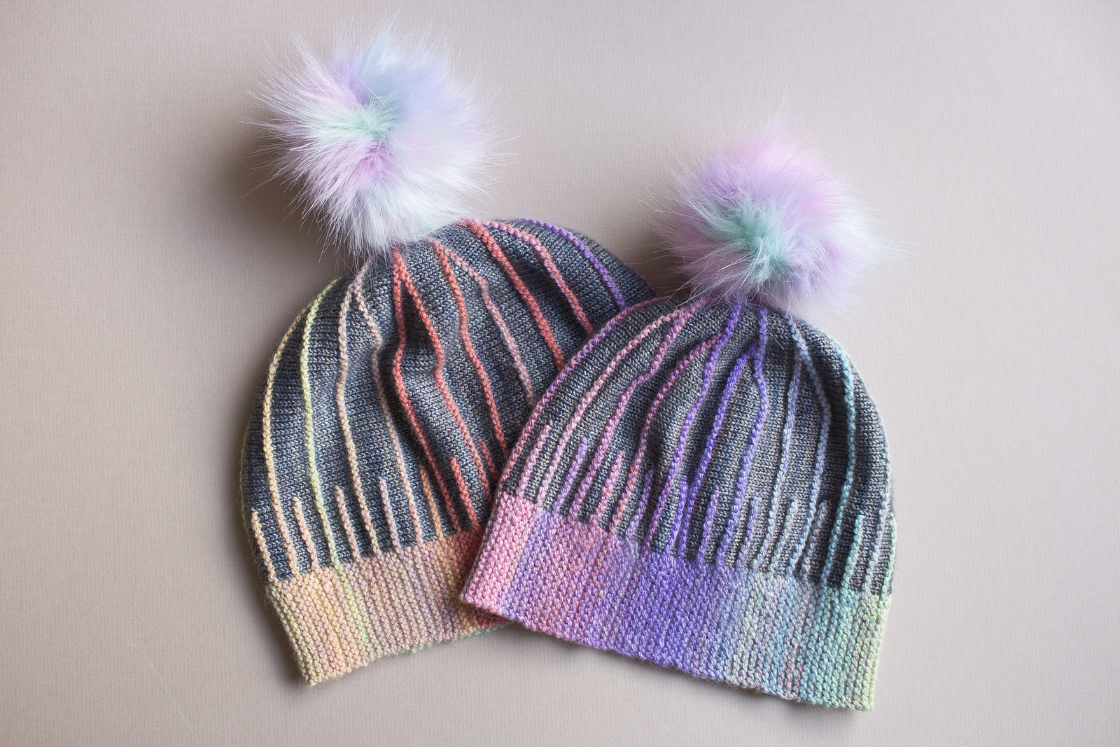 Two misura hats by Woolly Wormhead, knit by Mimi Codd from pastel handspun yarn and grey