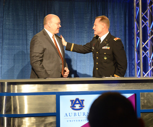 Christopher B. Roberts and Col. Eric Rannow greet each other on stage.
