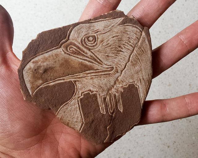 Piedra tallada de la cabeza de un aguila y la silueta de Monument Valley