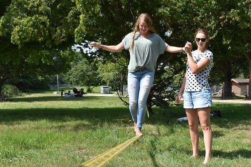 One student walks a slackline, while another watches