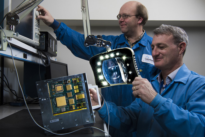 Paul Graham and Robert Merl work on the Low-Cost, Radiation-Hardened Single-Board Computer for Command and Data Handling both wearing blue lab coats