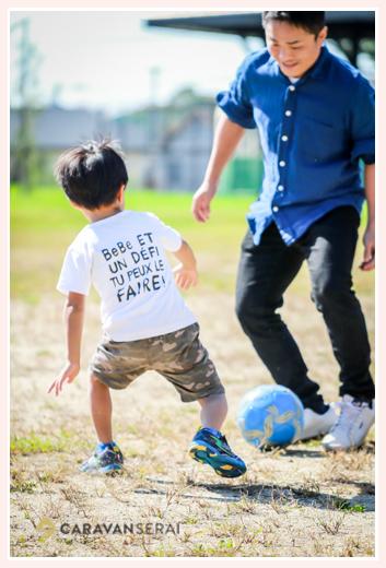 公園でパパとサッカーをする男の子
