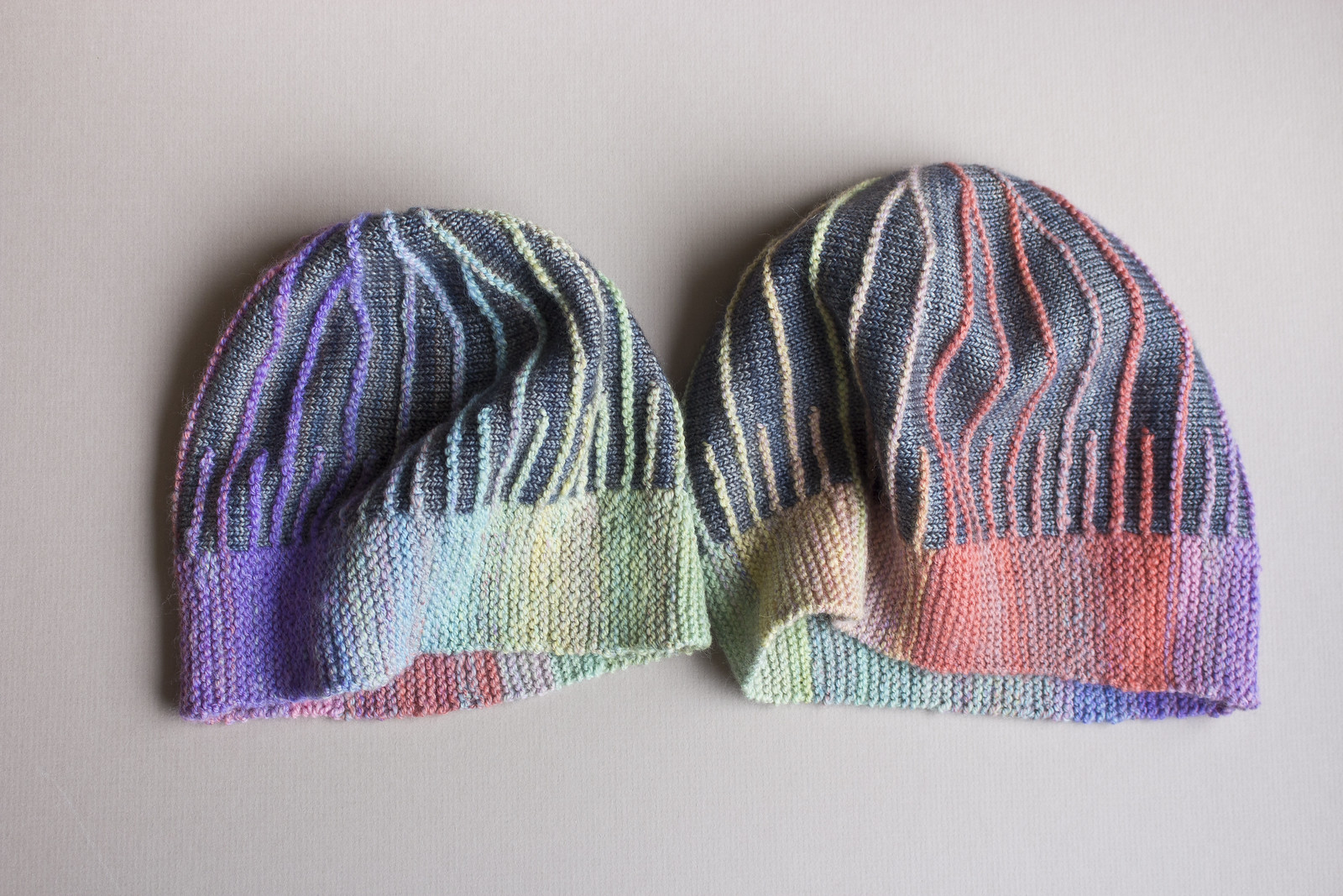 Two misura hats for toddler and adult knit from pastel handspun yarn with grey contrast