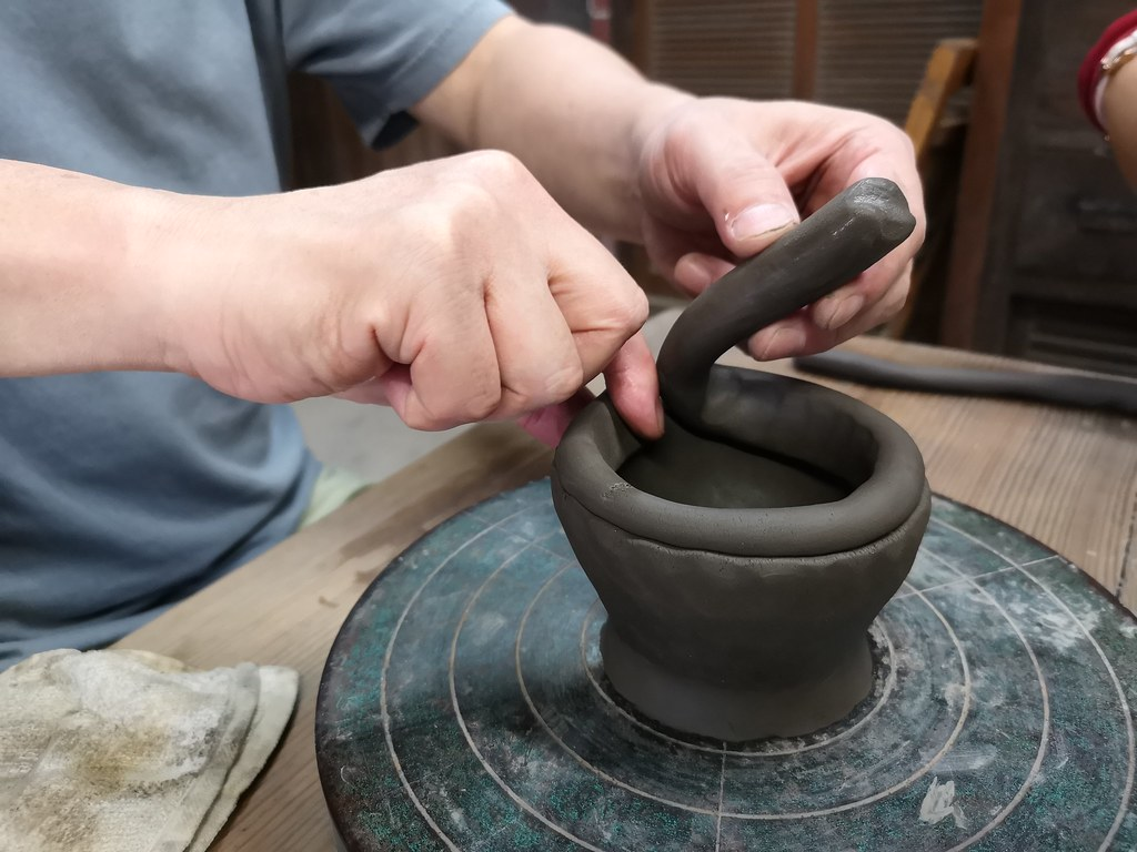 Sensei teaching us how to shape a bowl with clay.