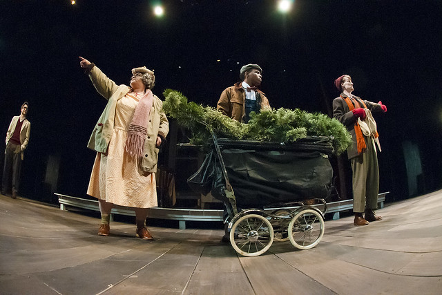 Three actors are on stage with a cart of Christmas decorations during a production of Holiday Memories.