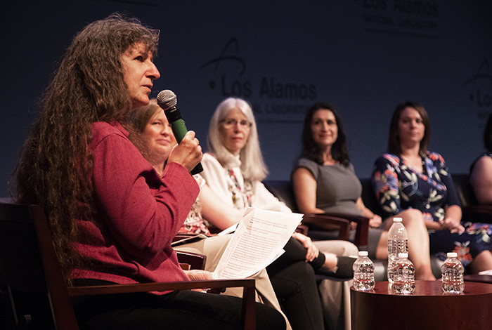 A woman holding a microphone speaks to other women seated in a semicircle.