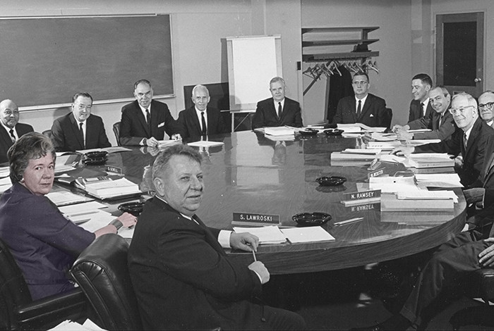 A group of men and a woman sitting at a table in a conference room look at the camera.