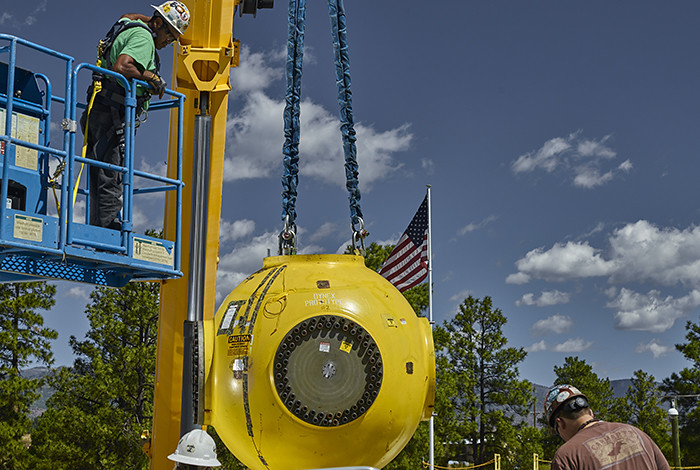 A piece of equipment is lowered by a crane while men in hard hats watch.