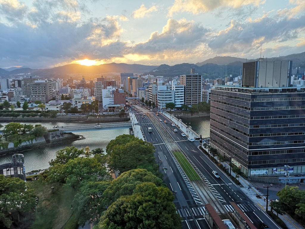 The sun disappears behind the hills outside the city area as we conclude our visit at the Hiroshima Orizuru Tower.