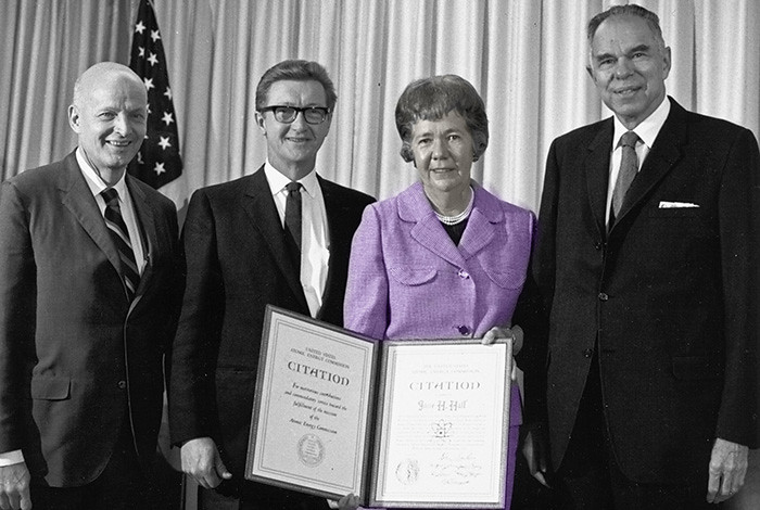 A woman holds a folder containing her AEC citation; men stand on both sides of her.