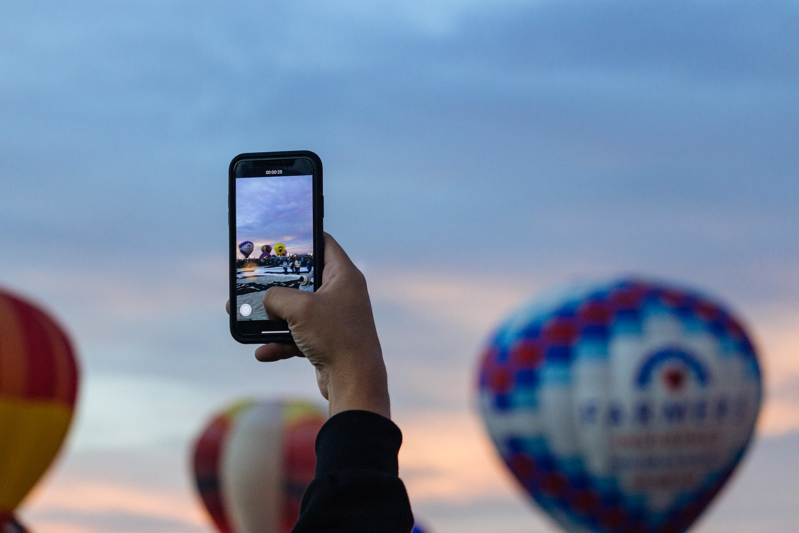 Person photographing balloons on their smartphone at the Albuquerque International Balloon Fiesta